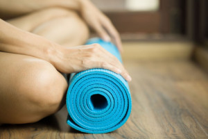 Young woman holding a yoga mat on the floor